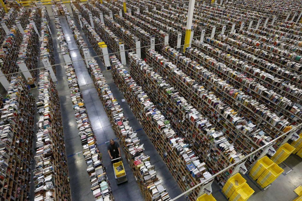 An Amazon employee walks down one of the miles of aisles at the company's fulfillment center in Phoenix.