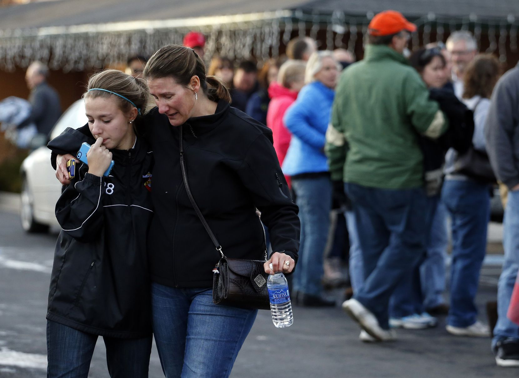 A parent picks up her daughter at a church where students from nearby Arapahoe High School were evacuated to after a shooting on the Centennial, Colo., campus Friday, Dec. 13, 2013. Arapahoe County Sheriff Grayson Robinson said the shooter shot two others at the school, before apparently killing himself. (AP Photo/Brennan Linsley)