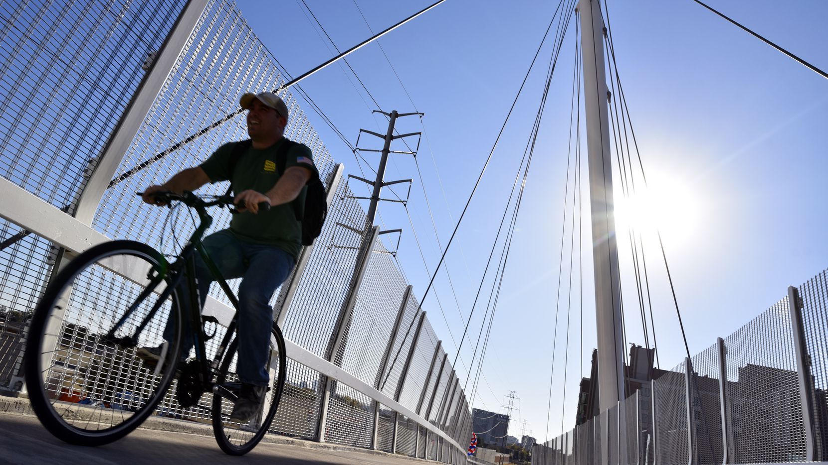 A man rides a bicycle on the new Mockingbird pedestrian bridge over Mockingbird Lane in Dallas, Thursday afternoon, Nov. 02, 2017. The 90-degree record was reached at 2 p.m. Thursday at DFW International Airport, but it kept getting warmer and topped out at 94 just after 4 p.m.
