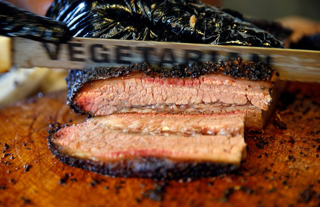 Panther City BBQ co-pitmasters Ernie Morales and Chris Magallanes cut brisket with a blade labeled Vegetarian in their trailer on Hattie St. in Fort Worth, Saturday, April 19, 2019. (Tom Fox/The Dallas Morning News)