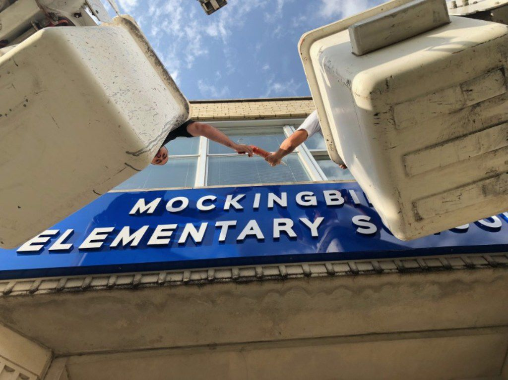 Workers install a new sign above the entrance of Dallas ISD's Stonewall Jackson Elementary, a campus located just off Mockingbird Lane in Old East Dallas. The school — which will be called Mockingbird Elementary as of July 1 — is one of four DISD schools being renamed this summer, removing names that honored Confederate leaders.
