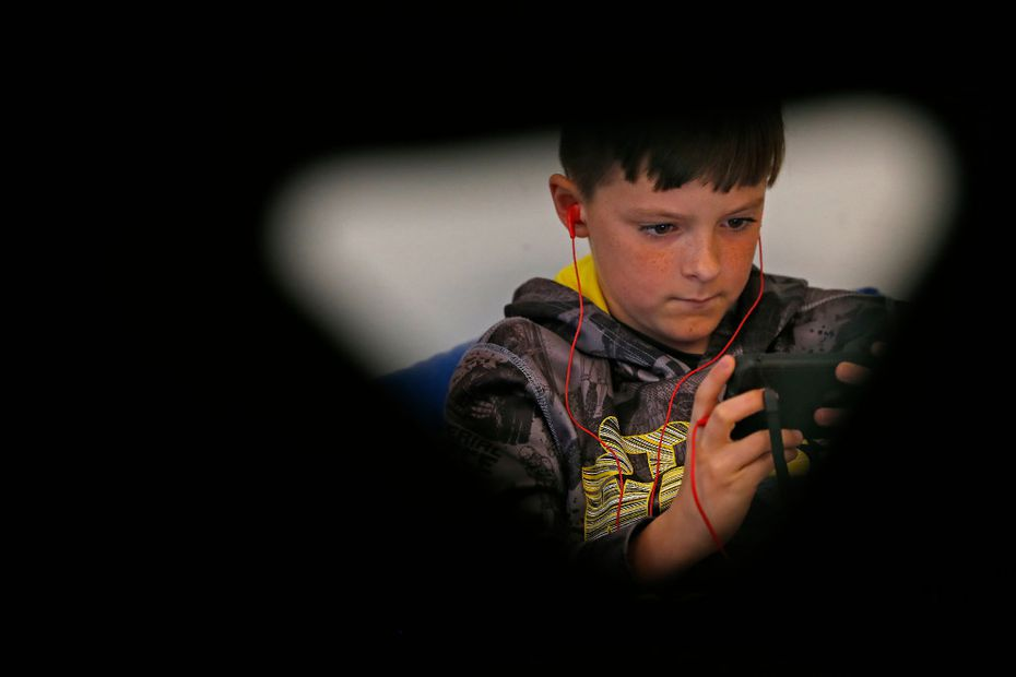 Fifth-grader Dakota Wood, 11, is seen through a classroom chair while he uses the Voice Dream Reader app at Griffis Elementary. (Jae S. Lee/Staff Photographer)