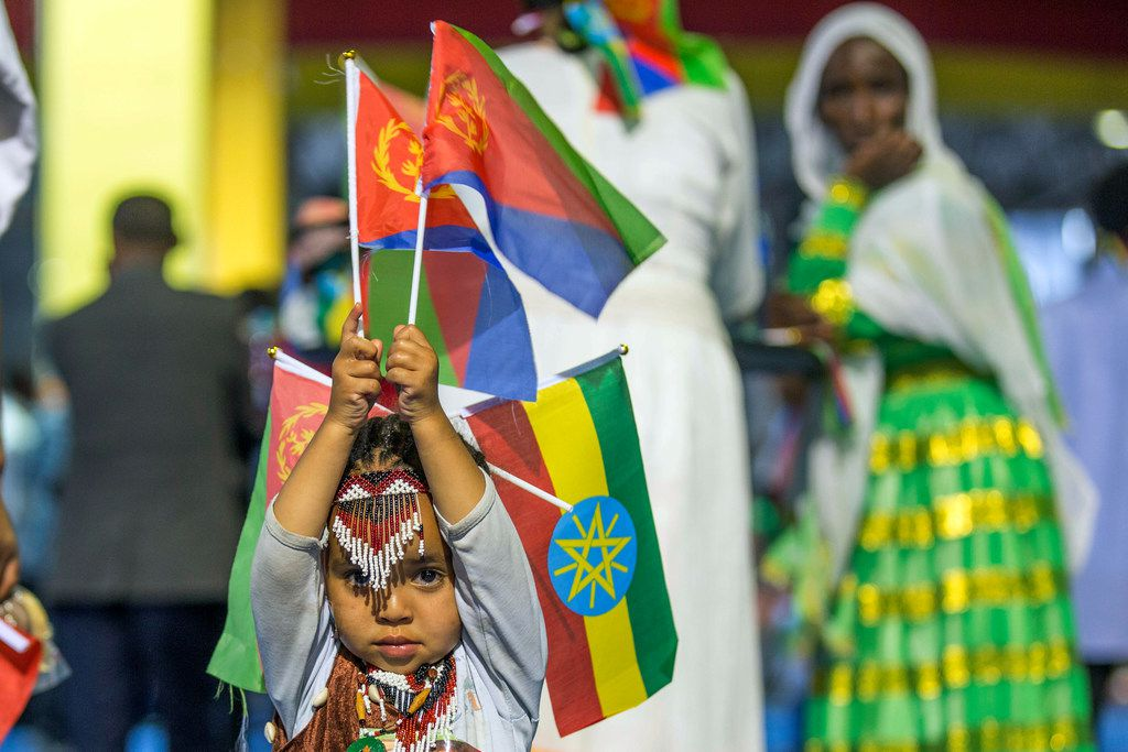 In this July 15, 2018 file photo, a child holds Ethiopian and Eritrean flags in the capital Addis Ababa, Ethiopia.