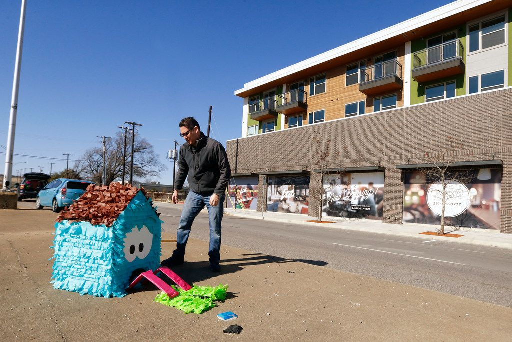 Dallas artist Giovanni Valderas places one of the pieces of his project called 'Casitas Tristas' on Fort Worth Drive in Dallas on Jan. 14