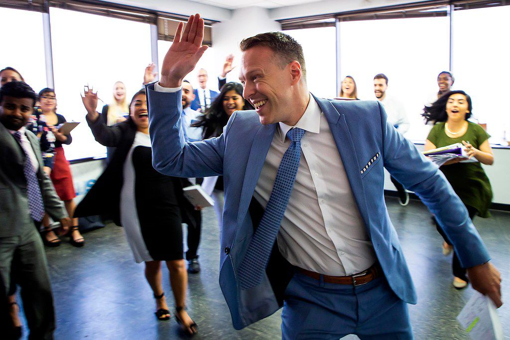 CEO Bart Yates runs to give a team member a high five during a marketing team meeting at CAM Partners on Friday, Sept. 7, 2018, in Dallas. (Smiley N. Pool/The Dallas Morning News)