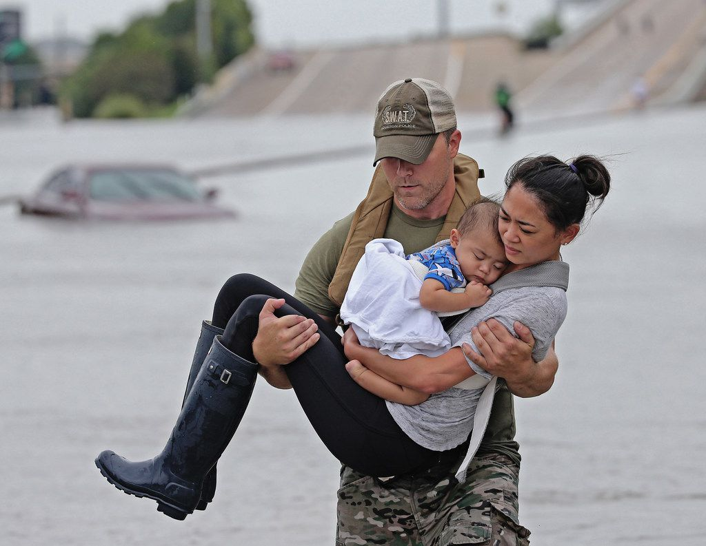 In this viral photo, Houston SWAT officer Daryl Hudeck carried Cathy Pham and then 13-month-old son, Aidan, to safety after they were rescued by boat from the flooding on Interstate 610 south in Houston on Aug. 27, 2017.