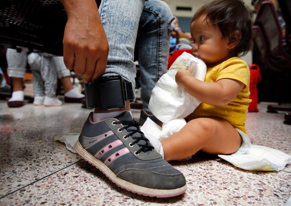 Damaris Gonzalez, 20, of Guatemala shows her ankle monitor that was attached by U.S. Border Patrol as they processed out of the McAllen, Texas facility. The monitor ensures that she will follow up to her court appointed hearing.  Damaris' father was killed and burned when she was younger. She and her 9 month-old son Yarlex (right) are waiting for their bus with other Central American immigrants at the Central Station bus terminal in downtown McAllen, Texas, Sunday, June 24, 2018. (Tom Fox/The Dallas Morning News)