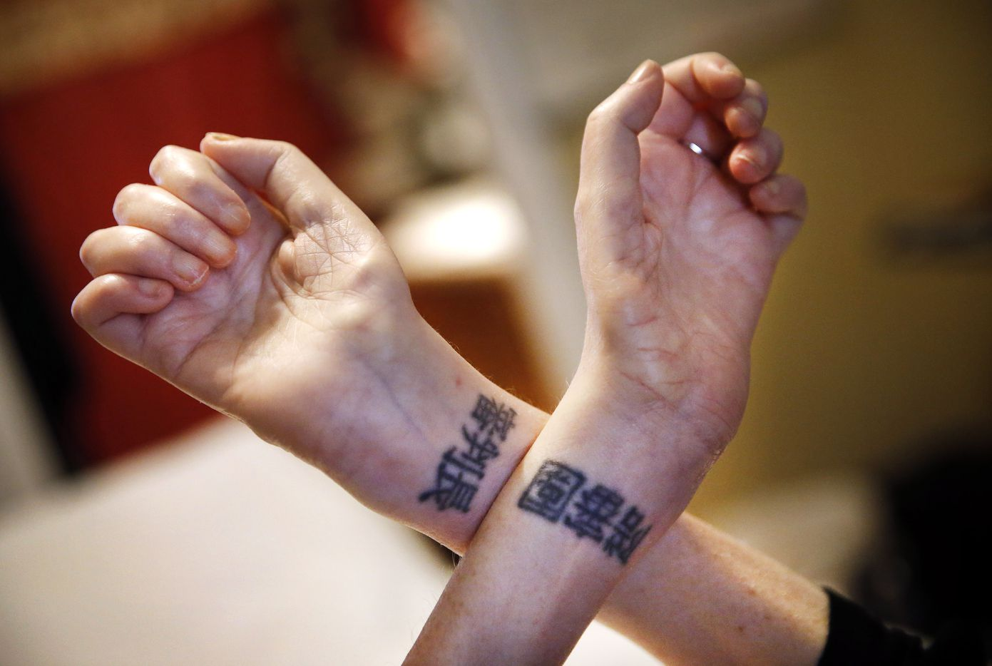 "Heather Powell says her tattoos, which she got as a young woman, mean ""Judge"" and ""Jury"" in Chinese."