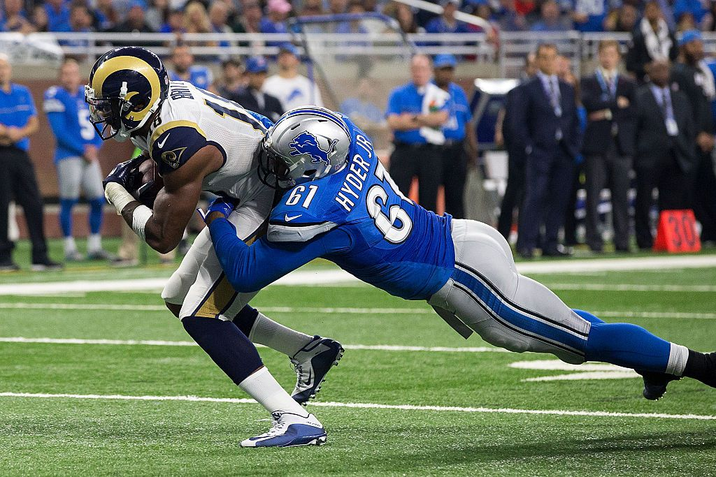 DETROIT, MI - OCTOBER 16: Wide receiver Kenny Britt #18 of the Los Angeles Rams runs with the football pulling defensive end Kerry Hyder #61 of the Detroit Lions for a fourth quarter touchdown during an NFL game at Ford Field on October 16, 2016 in Detroit, Michigan. (Photo by Dave Reginek/Getty Images)