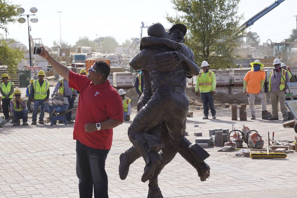 "Former Texas Ranger Bengie Molina takes a selfie in front of a statue ""Going To The Show"" during the unveiling at the new Globe Life Field in Arlington, Texas on August 7, 2018. Molina is one of the players featured in the statue."