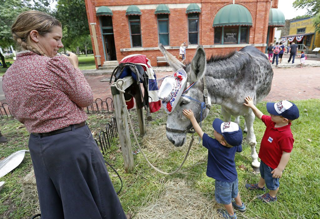 Bonnie Cooley (left), a history educator in charge of the animals, watched Eli Hall (right), and Ethan Hall, pet Nip during the Old Fashioned Fourth event at Dallas Heritage Village in Dallas. Will Willie and Waylon look as good in hats? That remains to be seen.