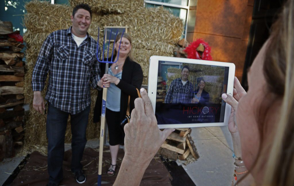 Carl and Joy Williams (left) hold for a photo by Jane Phillips in front of a haystack at the entrance of Hickory, Kent Rathbun's new restaurant in Plano.