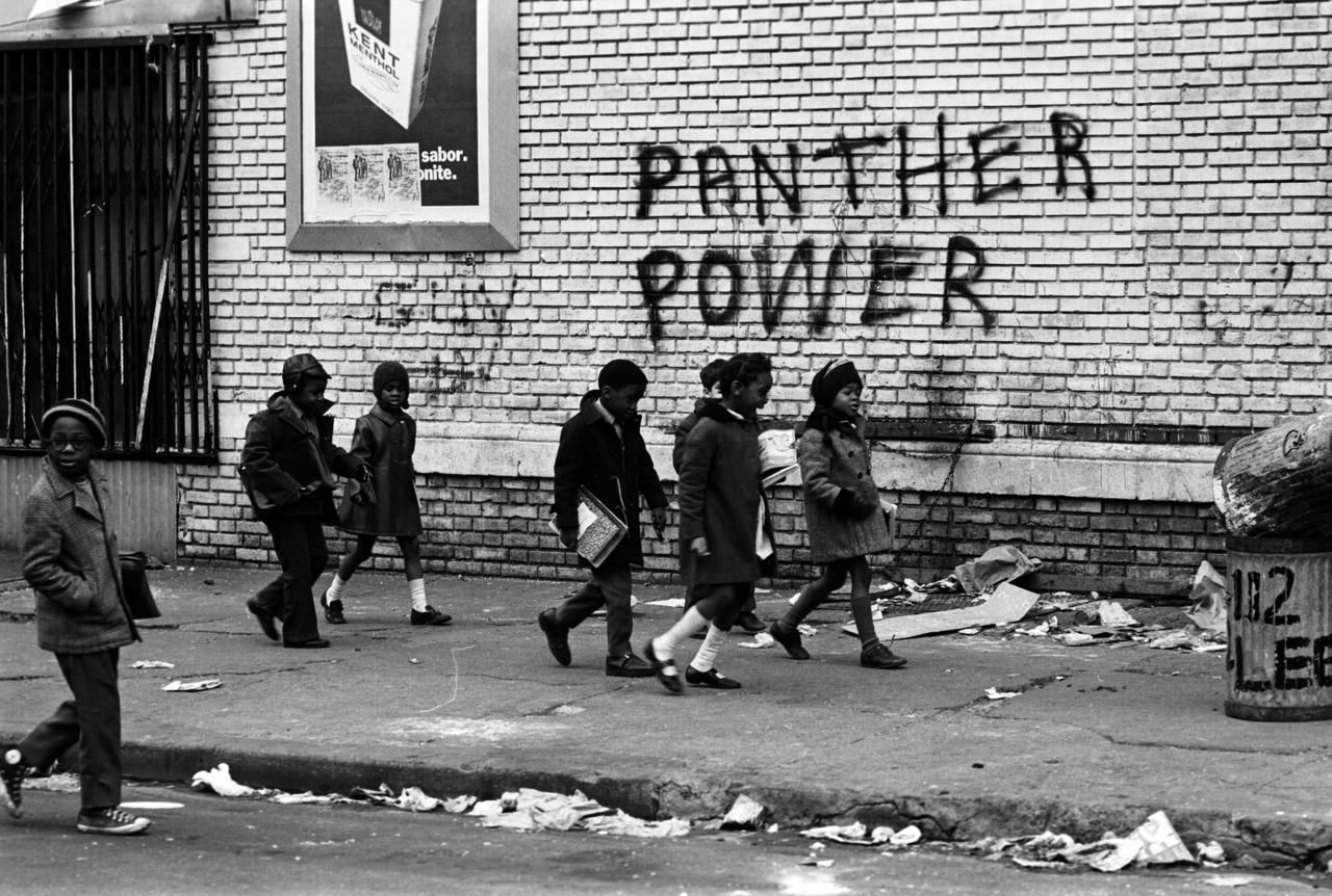 Children walk past Black Panthers graffiti in a scene from The Black Panthers: Vanguard of the Revolution.