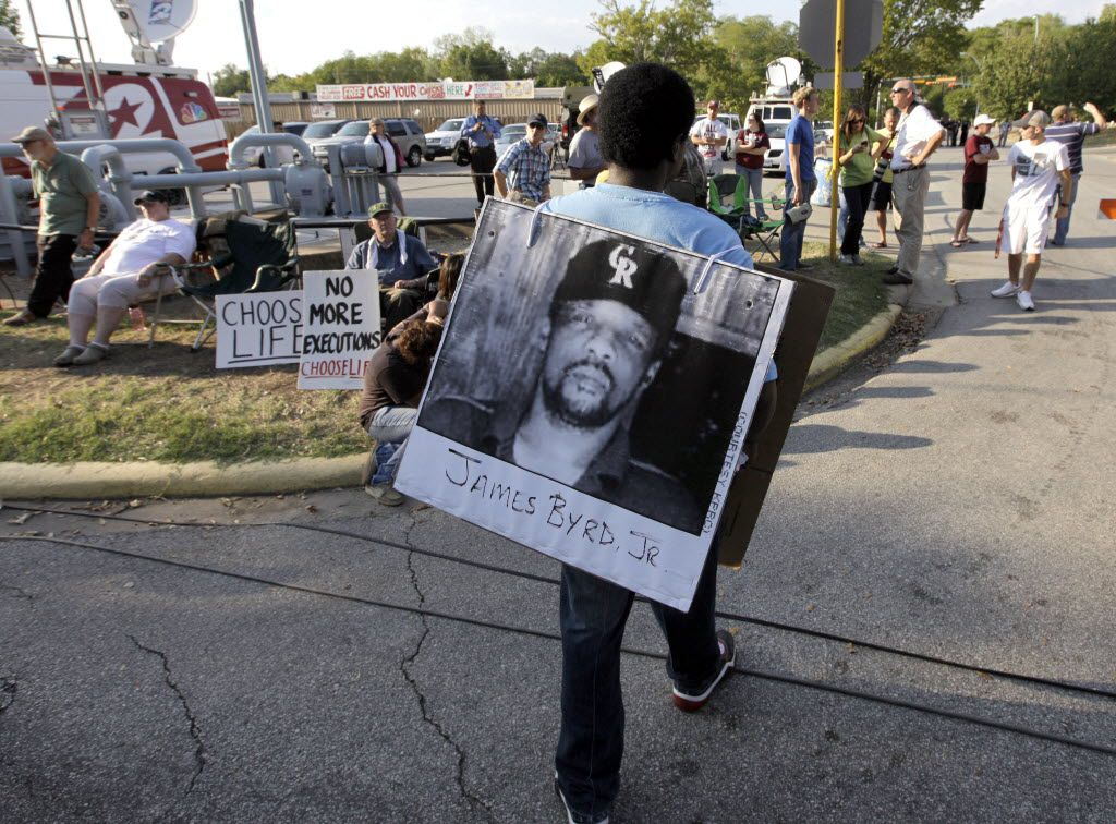 A man wore a placard with James Byrd Jr.'s photo outside the Texas Department of Criminal Justice Huntsville Unit before the 2011 execution of Lawrence Russell Brewer, one of three men convicted in Byrd's death.