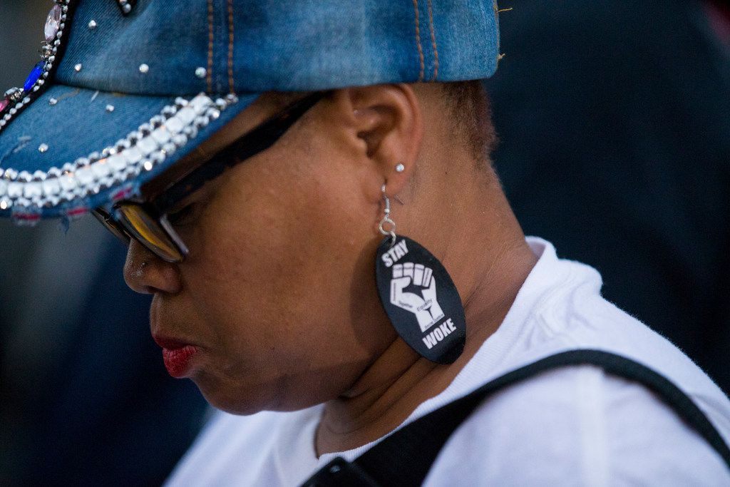 Dr. Pamela Grayson bows her head as she listens during a Mothers Against Police Brutality candlelight vigil on Sept. 7.