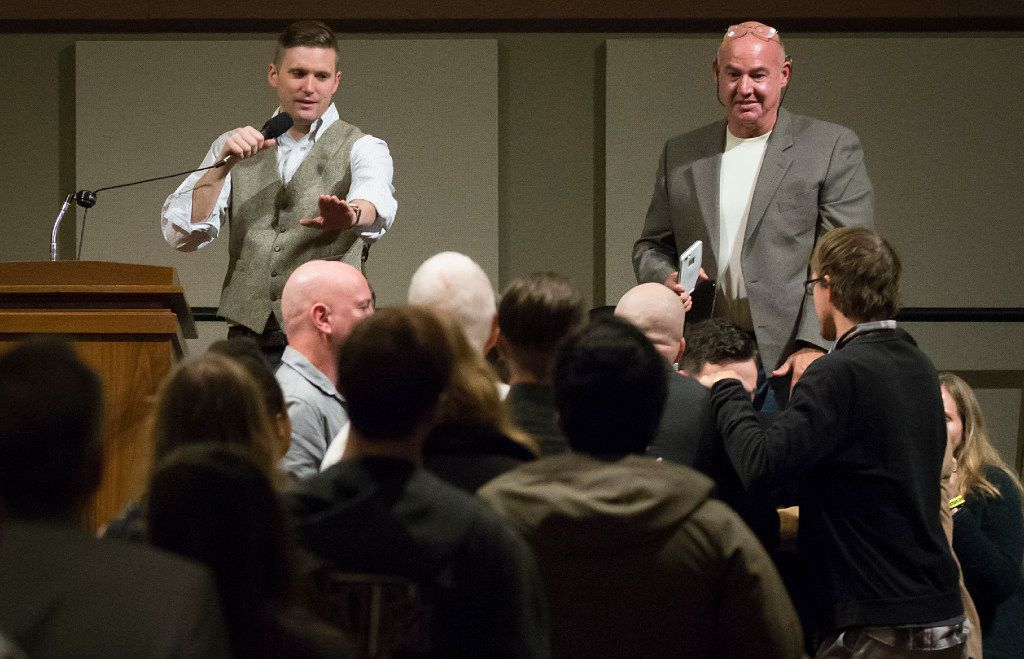 "Richard Spencer motions for calm as supporters and opponents scuffle in front of the stage while he speaks at the Memorial Student Center at Texas A&M University on Tuesday, Dec. 6, 2016, in College Station, Texas. Spencer, a Dallas native and a self-professed founder of the ""alt right"" movement, will speak at the campus at the invitation of a white nationalist and former student.  The university hosted the Aggies United event at Kyle Field, the university's football stadium, to overlap with Spencer's speech. (Smiley N. Pool/The Dallas Morning News)"