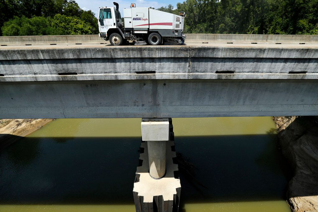 A street sweeper cleans the South Belt Line Road bridge crossing the Trinity River in Seagoville.