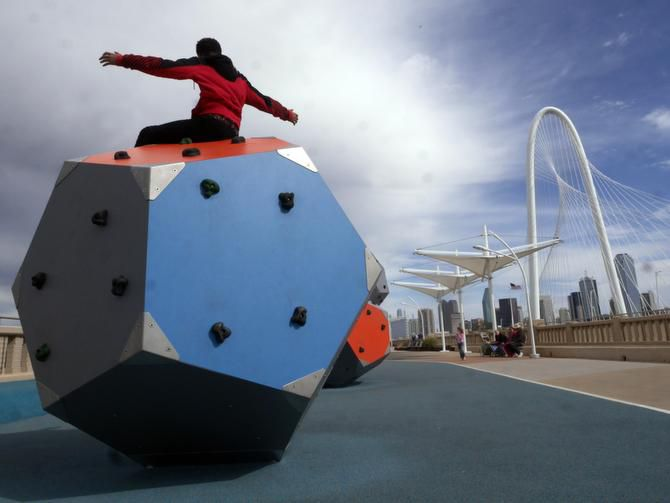 Kingdom Bankston, 13, raises his arms in victory after conquering a climbing cube in the play area of the bridge. The walkway is hampered in great part by the question of whether the Trinity toll road will one day run underneath it.