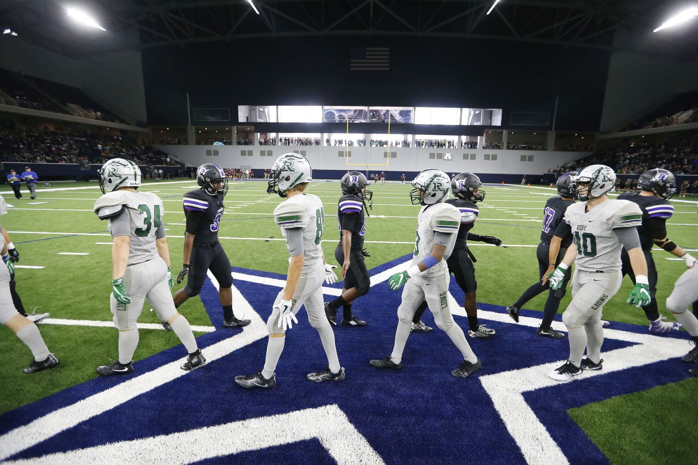 Independence High School and Reedy High School meet at the 50 yard line after playing in the first high school football game at The Star in Frisco on Saturday, August 27, 2016. (Vernon Bryant/The Dallas Morning News)