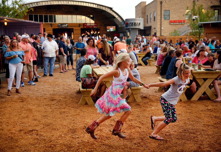 Nine year olds Avery Whipkey (left) and Maddox Snowden play in front of the main stage during opening night at ChopShop Live in Roanoke.