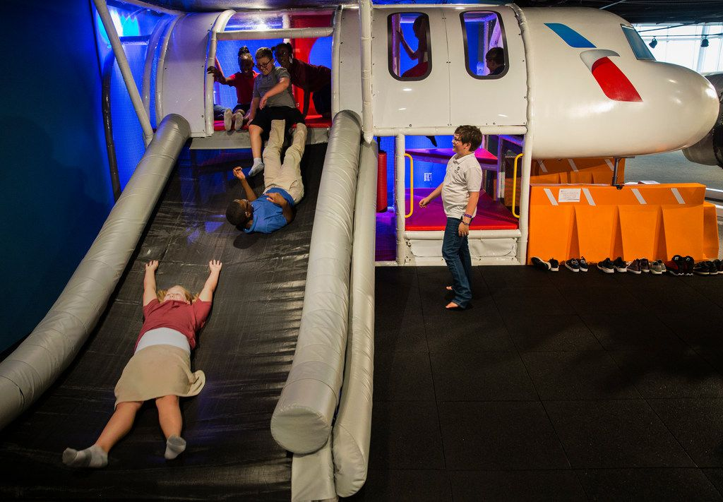 Ava Howard (bottom), 10, slides down a airplane evacuation playground with her classmates during a tour of American Airlines C.R. Smith Museum on Thursday, August 23, 2018 in Fort Worth. The newly renovated museum reopens Labor Day Weekend. (Ryan Michalesko/The Dallas Morning News)