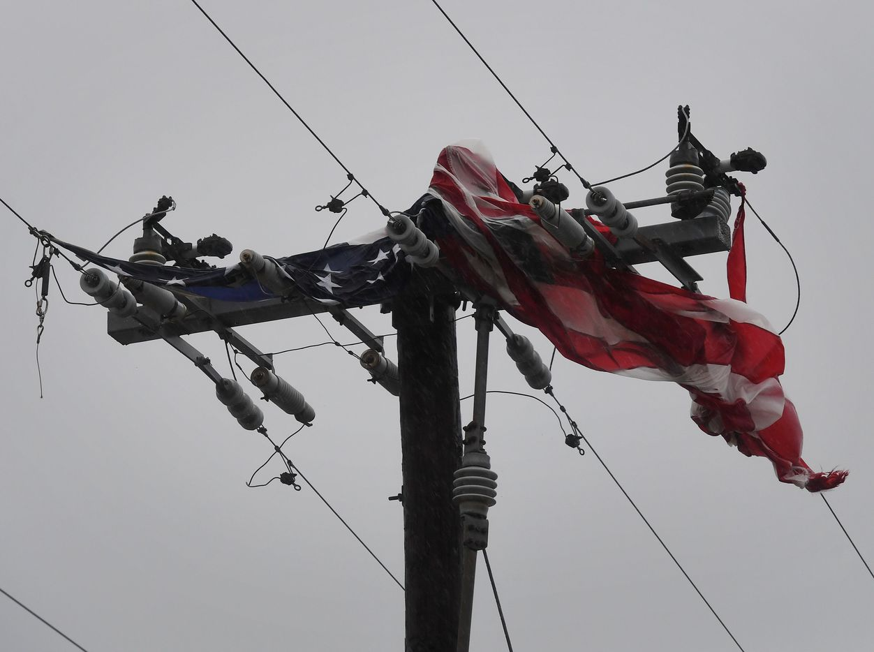 The US flag lies tangled in power lines as strong winds from Hurricane Harvey hits Corpus Christi, Texas on August 25, 2017.   Harvey on Friday further intensified into a dangerous category four storm, just hours before it was due to slam into the Texas coast, US meteorologists said.