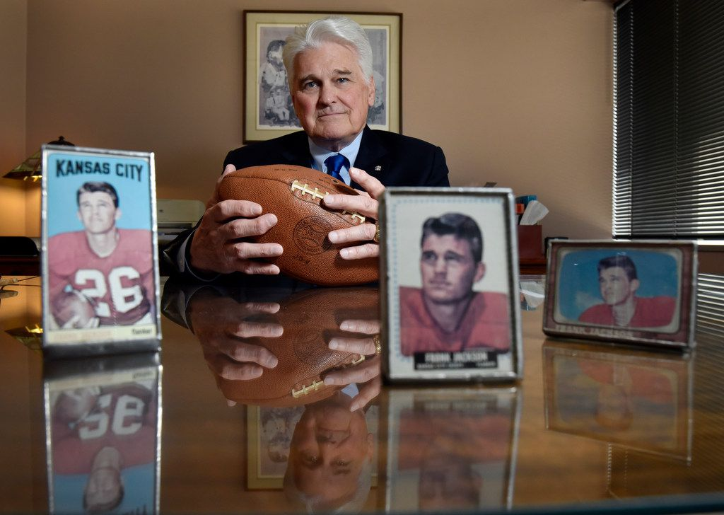 Frank Jackson, a criminal defense attorney and former NFL wide receiver, with a few of his football cards from the Kansas City Chiefs and Miami Dolphins, at his office in Dallas, Thursday afternoon June 07, 2018. Jackson is holding the game ball when scored a record for four touchdown receptions in a game. Jackson will be inducted into the Texas Criminal Defense Lawyers Association  Hall of Fame.