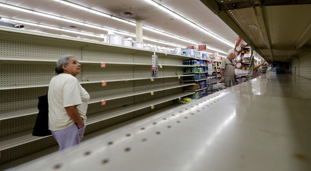 Shoppers pass empty shelves along the bottled water aisle in a Houston grocery store as Hurricane Harvey intensifies in the Gulf of Mexico on Aug. 24, 2017.