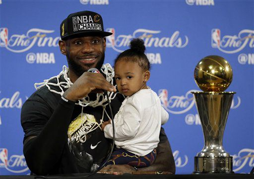 En esta foto de archivo del 19 de junio de 2016, el basquetbolista LeBron James sostiene a su hija Zhuri en una conferencia de prensa tras ganar el título de la NBA con los Cavaliers de Cleveland en Oakland, California. (AP Photo/Eric Risberg, File)