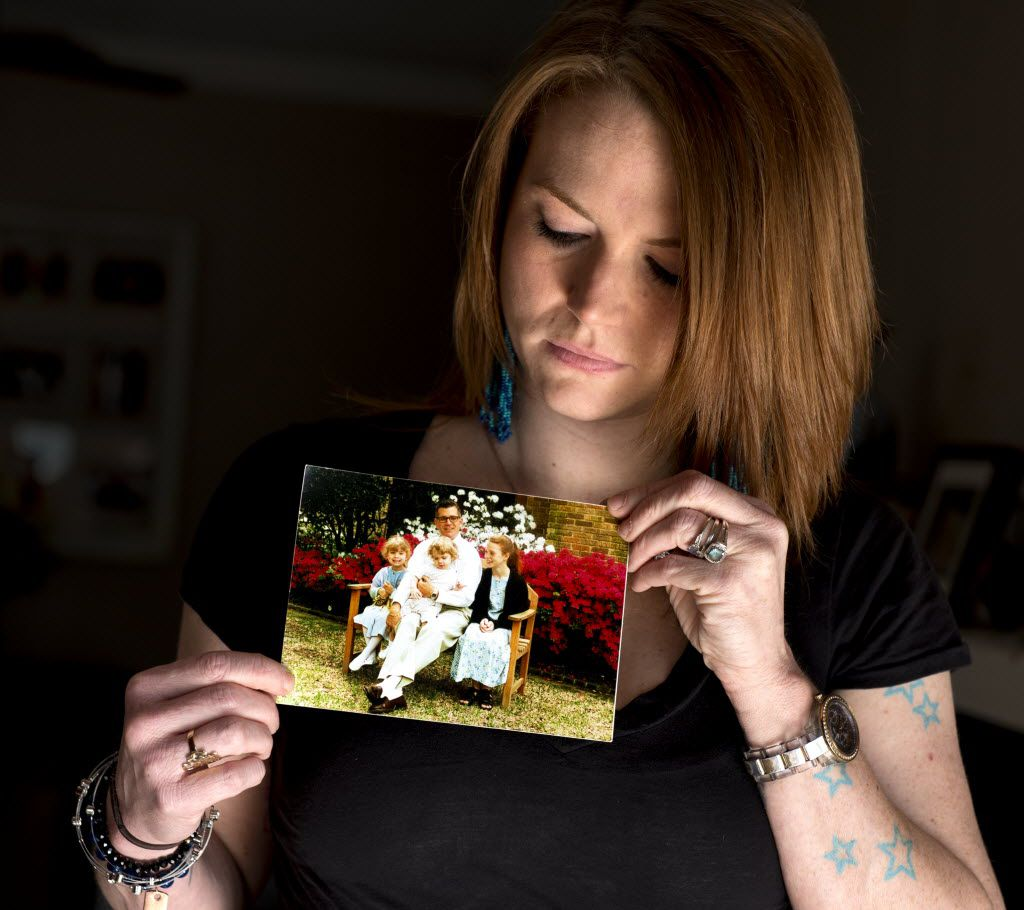 Christie Battaglia, daughter of convicted murderer John Battaglia, holds up a photo of her with her father and two half-sisters, Liberty and Faith. John Battaglia killed Faith, 9, and Liberty,6, in 2001 in his Dallas apartment while their mother listened on the phone. Christie Battaglia, a daughter from John's previous marriage, now resides in Baton Rouge, La.