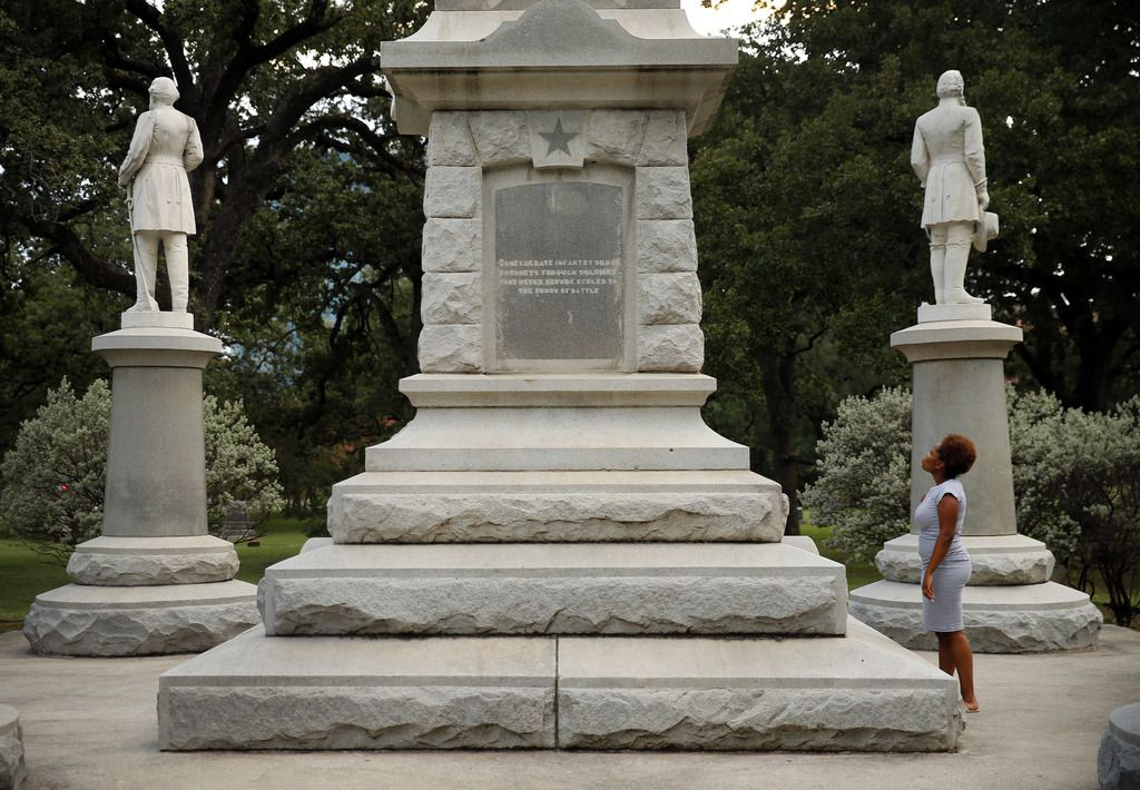 Victoria Miller of Dallas reads an inscription on the Confederate War Memorial in Pioneer Park cemetery in downtown Dallas.