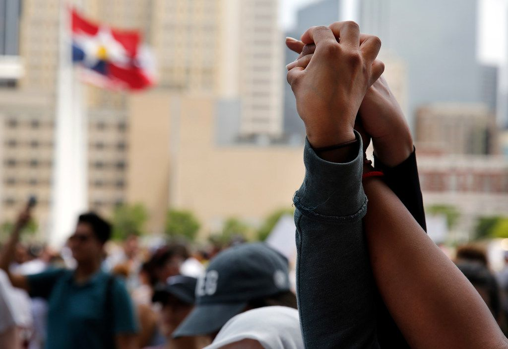 Protesters joined hands in solidarity during the downtown rally Saturday.
