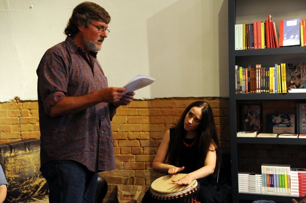 Tim Cloward reads poetry while wife Lisa Huffaker drums a rhythm at White Rock Zine Machine launch party at Deep Vellum Publishing in Dallas, TX on July 22, 2016. (Alexandra Olivia/ Special Contributor)