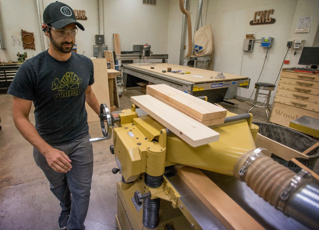 Andrew Zalaket puts wood through a planer for a project he's working on in the woodworking area of the Dallas Makersplace.