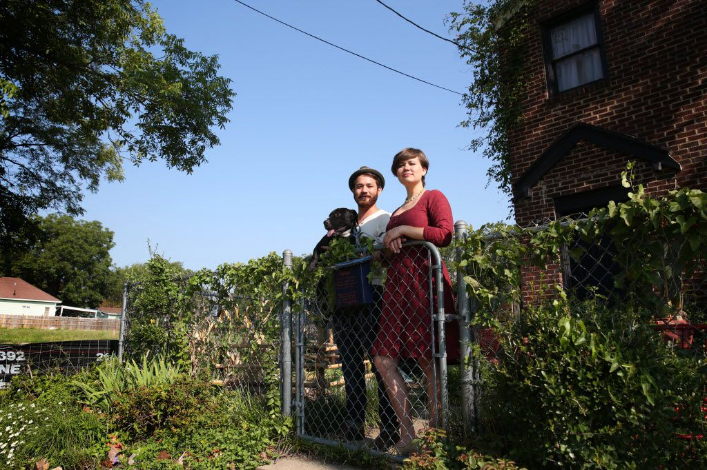 Sean Springer and Tracy Popken Springer, and their dog Sir Robin, in front of the house they refuse to sell to developers taking over the neighborhood surrounding Bishop Arts.