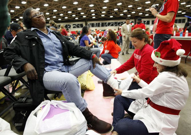 Volunteer Kathleen Turner helped Earnestine Hadnot try on a pair of shoes at Christmas Gift for the Homeless, held Saturday at the Dallas Convention Center. The event was expected to draw 10,000 people, including 5,000 children.