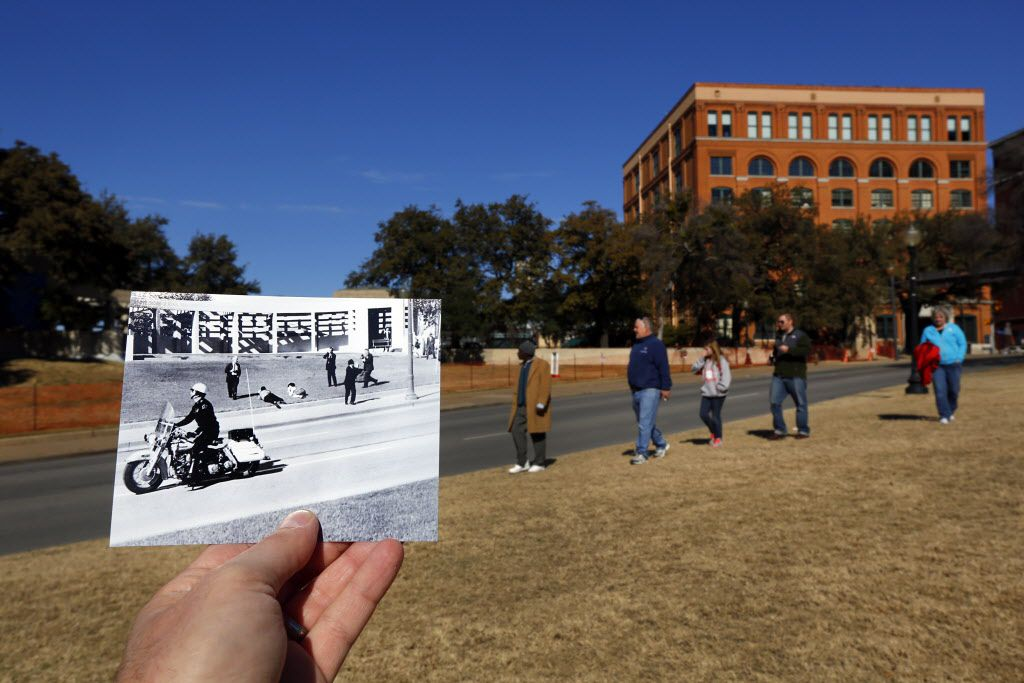 Tourists (right) gaze toward the grassy knoll at Dealey Plaza, Thursday, January  3, 2013, as they learn about the assassination of Pres. John F. Kennedy, juxtaposed to a photo taken nearly 50 years ago on Nov. 22, 1963 as Bill and Gayle Newman dove on the ground to shield their children with their bodies as Dallas Police officers and the speeding motorcade passed seconds after the president was shot.