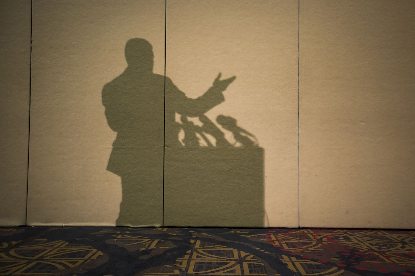 Richard Spencer casts a shadow on the wall as he addresses the media during a news conference before his speech.
