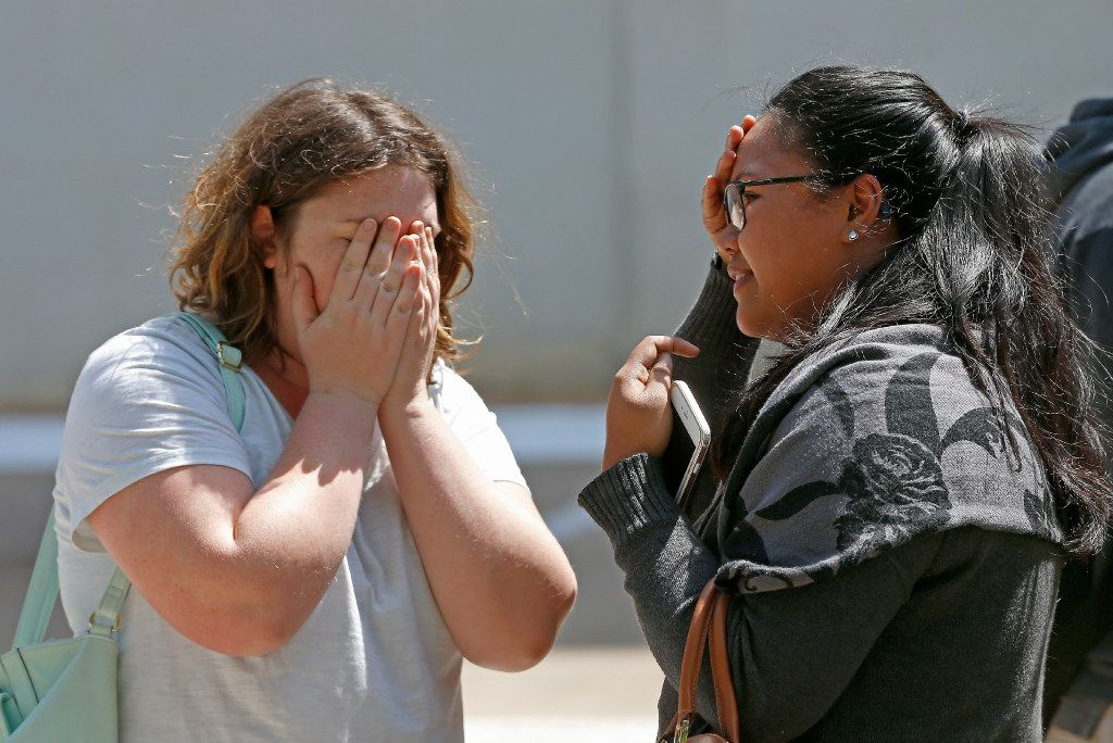 Camille Crowe (left) covers her face while talking with Tran Vu outside an office building in Lake Highlands near the High Five where police found two people dead inside the office building in Dallas, Monday, April 24, 2017. Crowe (Jae S. Lee/The Dallas Morning News)
