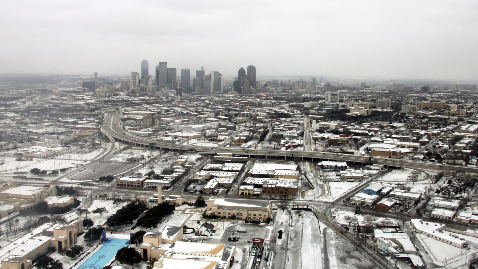 An aerial view of the snow with the Dallas skyline in the background.
