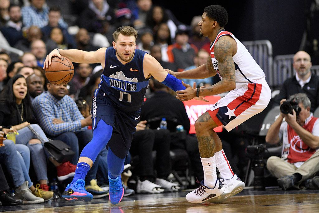 Dallas Mavericks forward Luka Doncic (77) dribbles the ball next to Washington Wizards guard Bradley Beal during the second half of an NBA basketball game Wednesday, March 6, 2019, in Washington. The Wizards won 132-123. (AP Photo/Nick Wass)