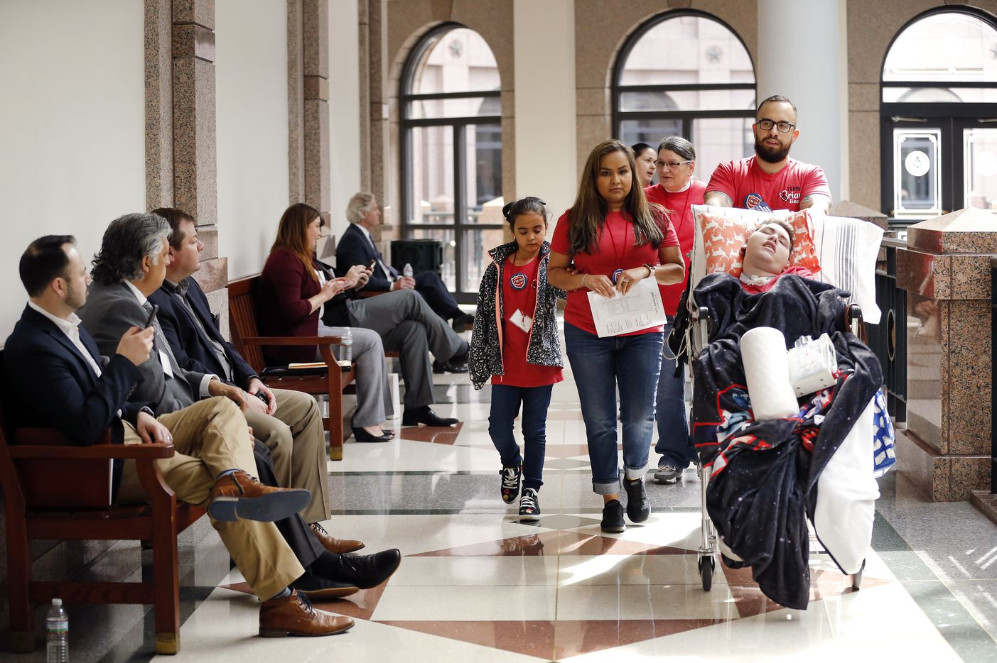 Gabriella McCann of Bulverde, Texas (center) and her medically fragile son, Briar, 15, (being pushed by his LVN Gregory Flores) head to a visit with State Senator Peter Flores, R-District 19.