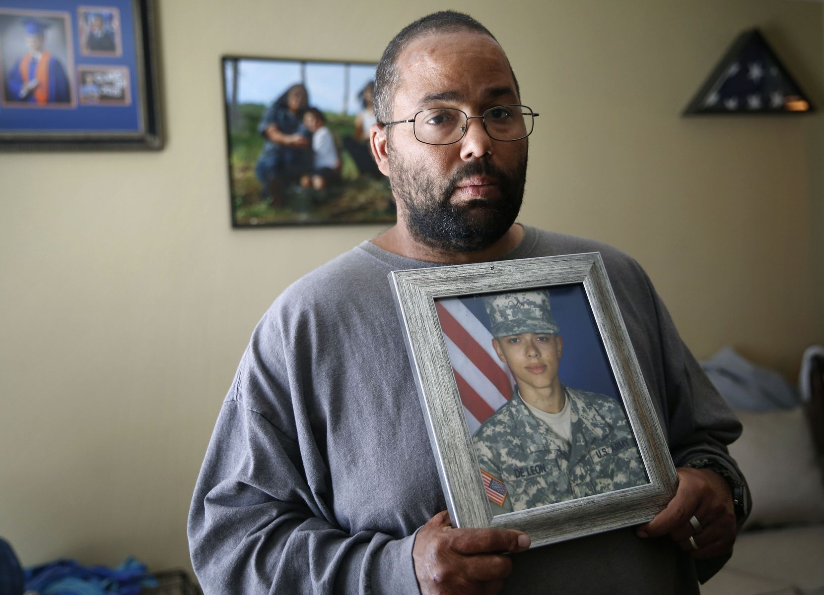 Ricky DeLeon holds a portrait of his late son, Isaac Lee DeLeon, at his home in San Angelo.