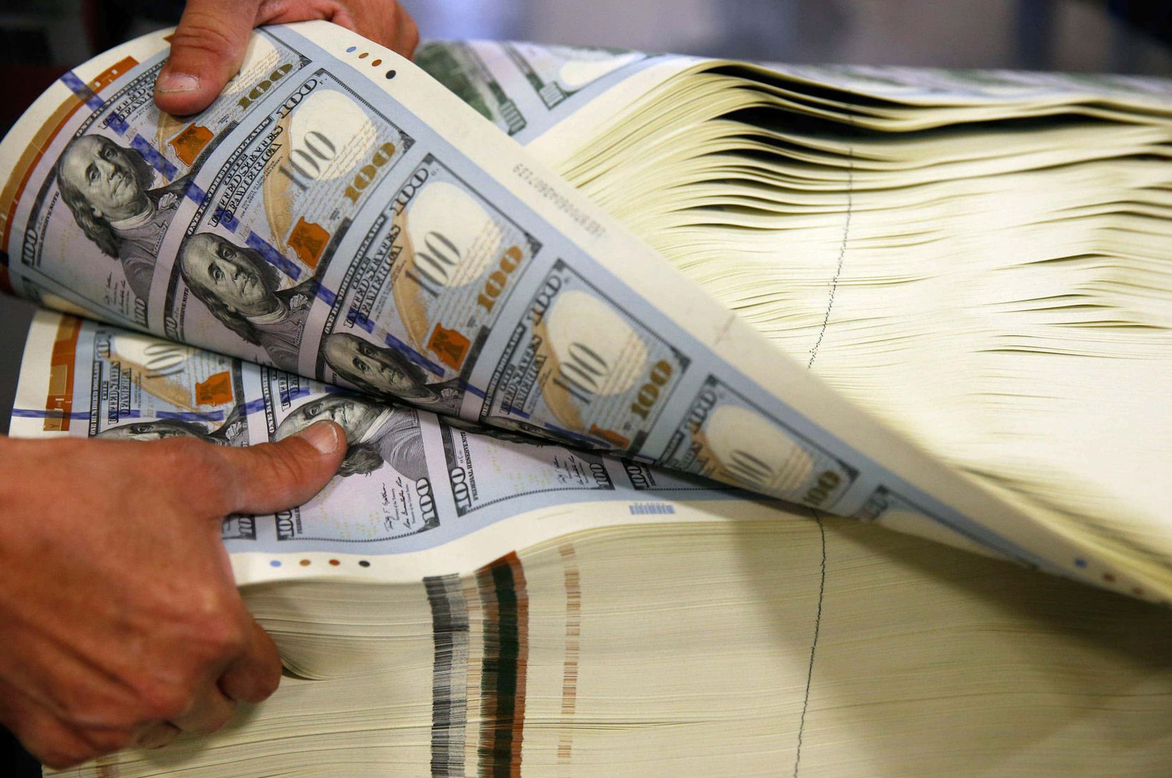 Juan Reyna aerates a stack of $100 notes to help keep them from causing a paper jam in the U.S. Bureau of Engraving and Printing's inspection machinery. A lot of money is printed there, but it's free to tour the facility.