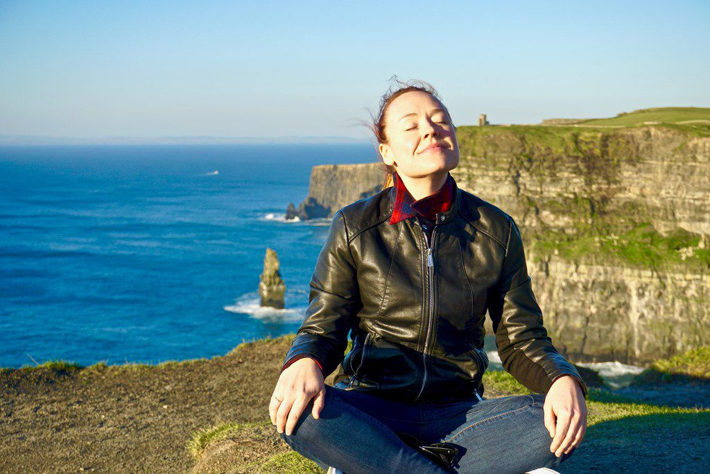 Lauren McGaughy meditates near the edge of the Cliffs of Moher, with O'Brien's Tower off in the distance.