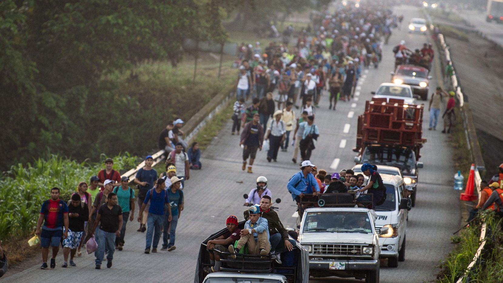 Migrantes hondureños caminan junto a vehículos que transportan a personas desde Chiapas, México, en su trayecto hacia el norte. (AFP/Getty Images/PEDRO PARDO)