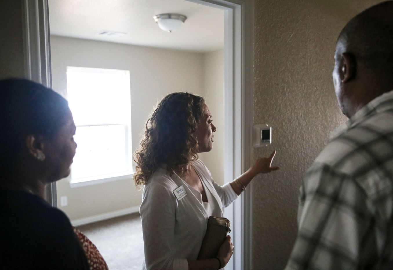 Habitat for Humanity Senior Director of Home Owner Services Blaine Cowart, center, shows new homeowners Tequadesh Eshibelachew, left, and Terefe Bezabeh how to use a programable thermostat during a walk through their Habitat for Humanity built West Dallas home Thursday, Aug. 8, 2019 in Dallas.