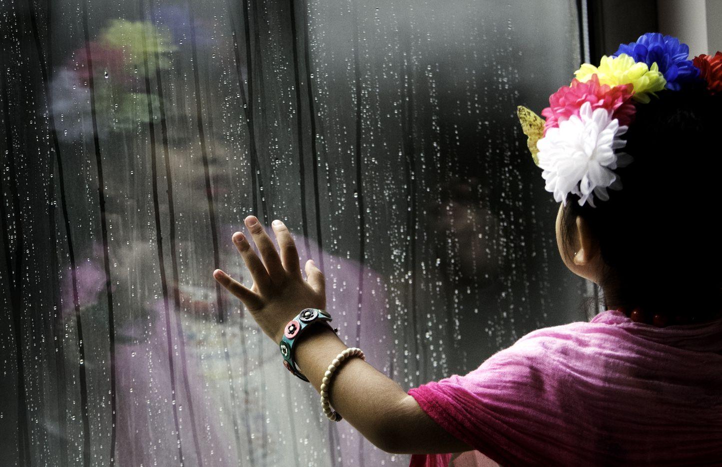 Marley Leyva, 4, watches rain roll down a window during the Frida Fest.