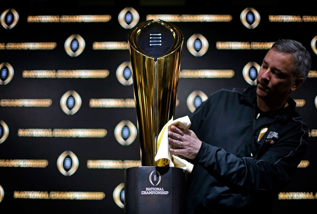 FILE - In this Jan. 7, 2018 file photo Charley Green buffs the NCAA college football championship trophy before a coaches news conference in Atlanta. (AP Photo/David Goldman, file)