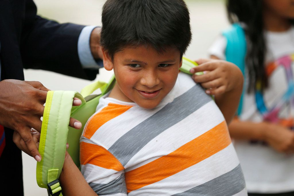 Apolinar Lopez, 8, tries on a new backpack from Adan Gonzalez, third-grade teacher at Bowie Elementary, and executive director of Puede Network. (Rose Baca/The Dallas Morning News)